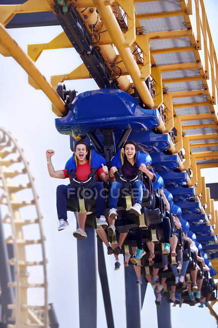 Young man cheering on amusement park ride — Stock Photo