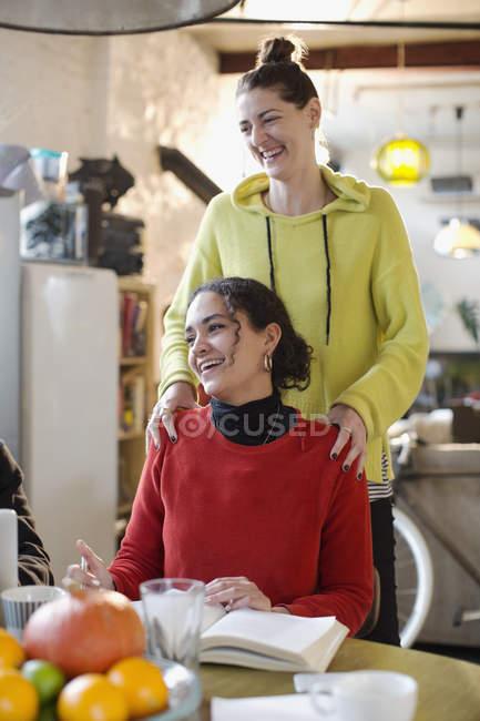 Усміхаючись молоді жінки друзі в квартирі — стокове фото