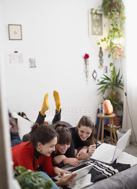 Junge weibliche College-Studenten studieren, mit digitalen Tablet und Laptop auf Bett — Stockfoto