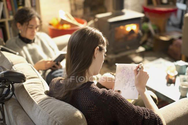 Junge Frau zeichnen, skizzieren im Editor im Wohnzimmer — Stockfoto