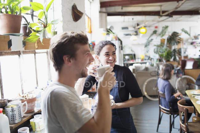 Щасливі сусіди по кімнаті, насолоджуючись Кава у квартирі-кухня — стокове фото
