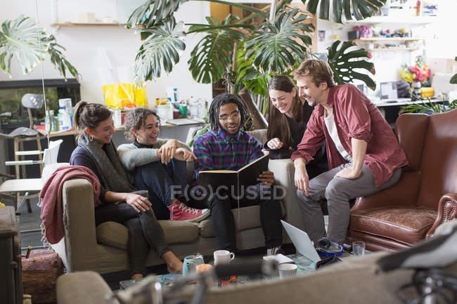Amici di giovane adulto coinquilino lettura libro in appartamento soggiorno — Foto stock