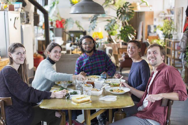 Ritratto sorridente, fiducioso giovane compagno adulto amici che godono del pranzo al tavolo Appartamento — Foto stock