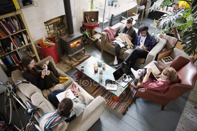 Amici di giovane adulto coinquilino appendere fuori in appartamento soggiorno — Foto stock