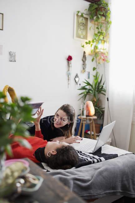 Jovens amigas saindo, usando laptop e tablet digital na cama — Fotografia de Stock