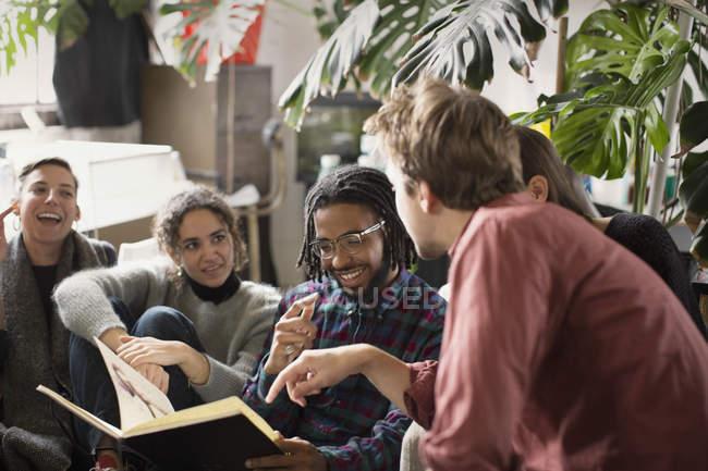 Jungen Erwachsenen Mitbewohner Freunde betrachten Skizzenbuch im Wohnzimmer — Stockfoto