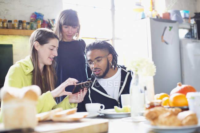 Amici di giovane adulto coinquilino utilizzando smart phone al tavolo della colazione in appartamento — Foto stock