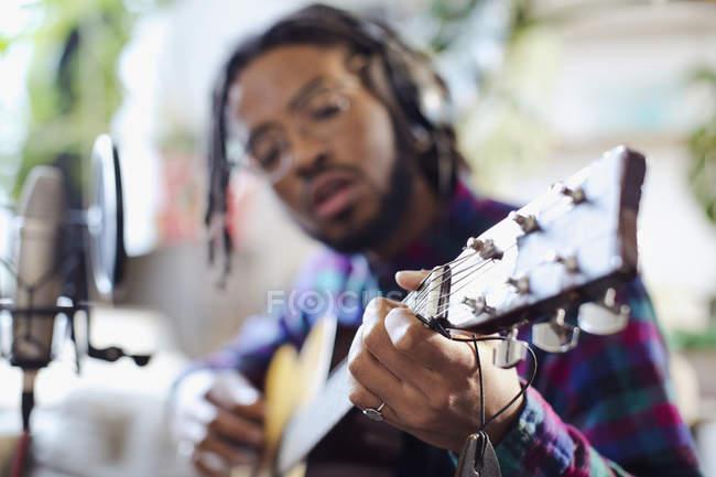 Junge männliche Musiker aufnehmen von Musik, Gitarre spielen, am Mikrofon — Stockfoto