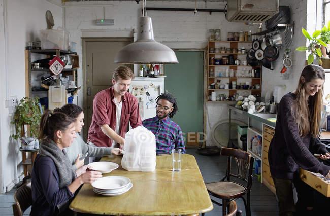 Amici di giovane adulto coinquilino preparando a mangiare cibo da asporto in appartamento cucina — Foto stock