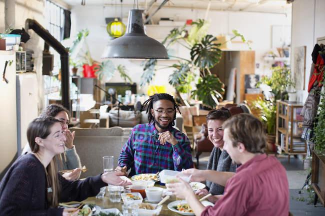 Amici di giovane adulto coinquilino che godono di alimento da portar via al tavolo di cucina in appartamento — Foto stock