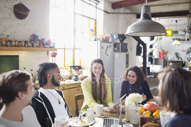 Amici di giovane adulto coinquilino utilizzando digital tablet e laptop al tavolo della colazione in appartamento — Foto stock