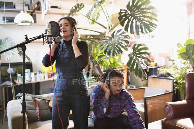 Junger Mann und Frau Musikaufnahmen in Wohnung, ins Mikrofon singen — Stockfoto