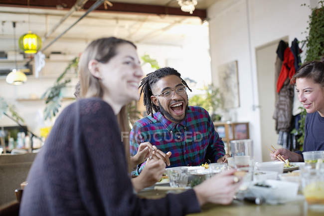 Happy young adult roommates eating take out food at kitchen table in apartment — Stock Photo