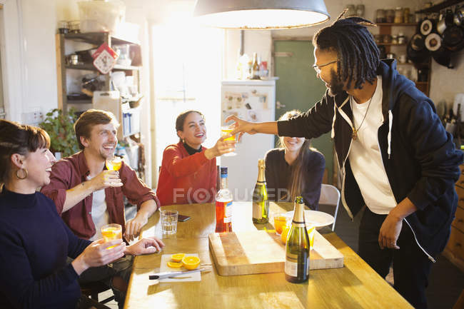 Young adult friends enjoying cocktails at apartment kitchen table — Stock Photo