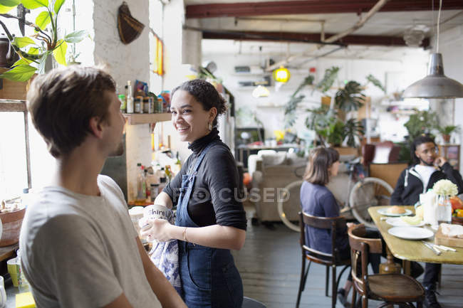 Друзьями молодой сосед делает блюда и говорить в кухне — стоковое фото