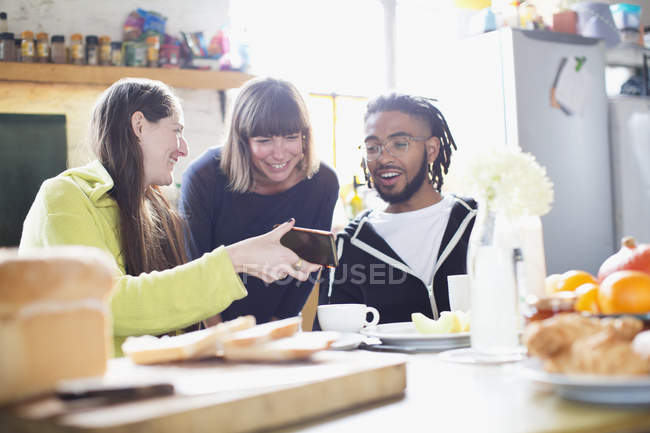 Young roommate friends using smart phone at breakfast table in apartment — Stock Photo