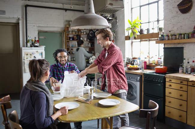 Amigos do jovem colega de quarto se preparando para comer a comida na mesa de cozinha no apartamento — Fotografia de Stock