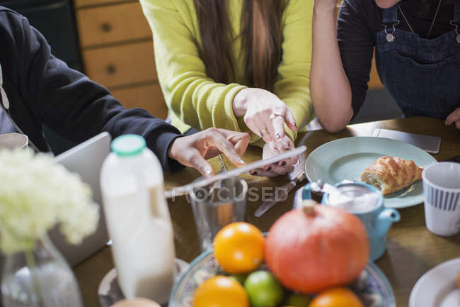Roommate friends using digital tablet at breakfast table — Stock Photo