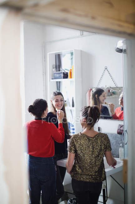 Young women friends getting ready, applying makeup in bathroom — Stock Photo