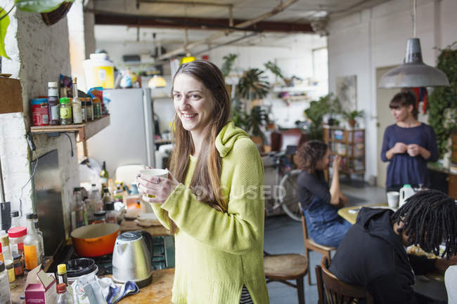 Smiling young woman drinking coffee with roommates in apartment kitchen — Stock Photo