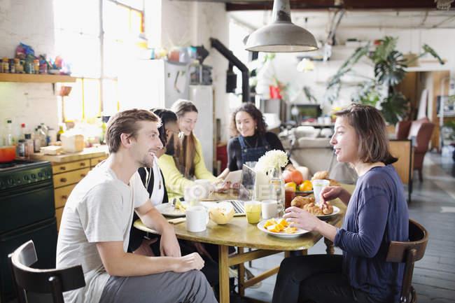 Amici del giovane compagno di stanza godendo colazione al tavolo di cucina in appartamento — Foto stock
