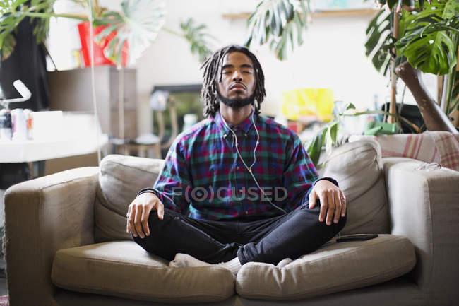 Jovem sereno meditando com fones de ouvido no sofá do apartamento — Fotografia de Stock