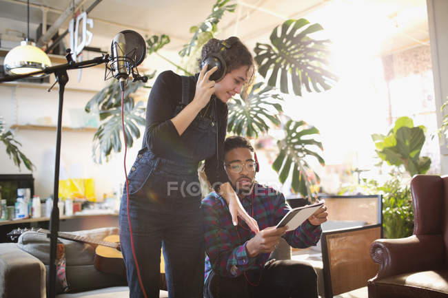 Young man and woman recording music in apartment — Stock Photo