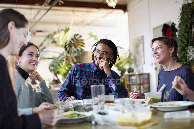 Young roommate friends enjoying takeout food at kitchen table in apartment — Stock Photo