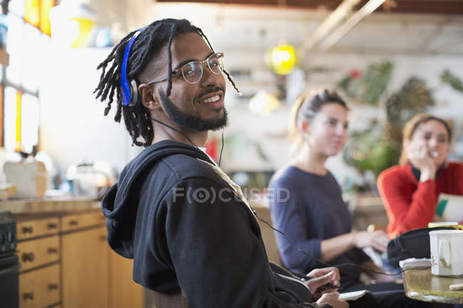 Portrait smiling young man with headphones at kitchen table — Stock Photo