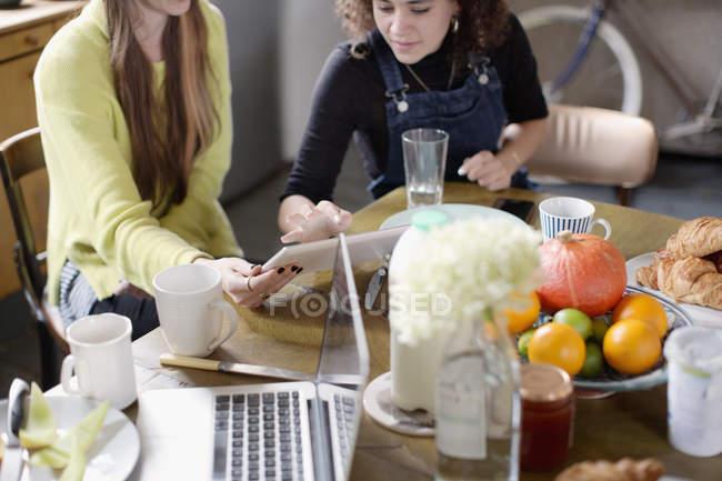 Amici di coinquilino delle giovani donne utilizzando la tavoletta digitale al tavolo colazione — Foto stock