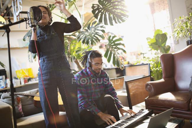 Молодой мужчина и женщина запись музыки, петь и играть на пианино в квартире — стоковое фото