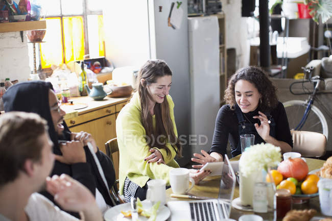 Young roommate friends using digital tablet and laptop at breakfast table in apartment — Stock Photo