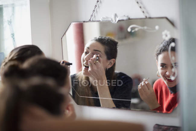 Young women friends getting ready, applying makeup in bathroom mirror — Stock Photo