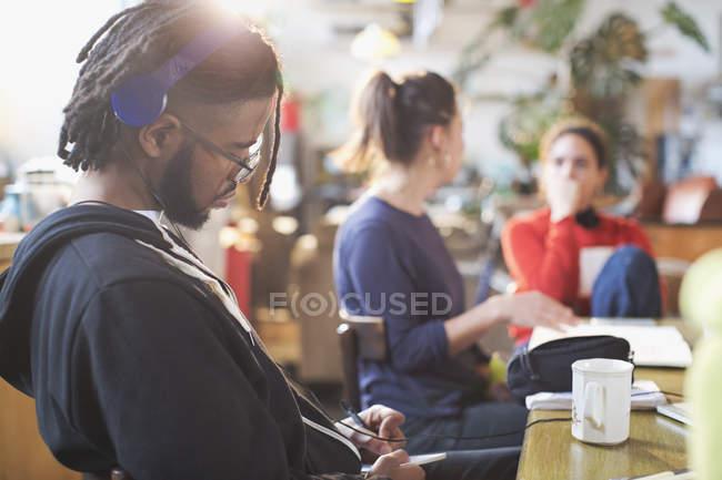 Молода людина з навушниками навчається в кухонному столі — стокове фото