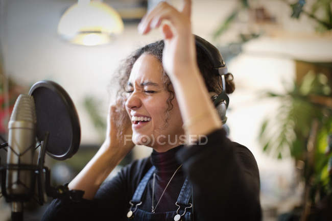 Young woman recording music, singing into microphone — Stock Photo