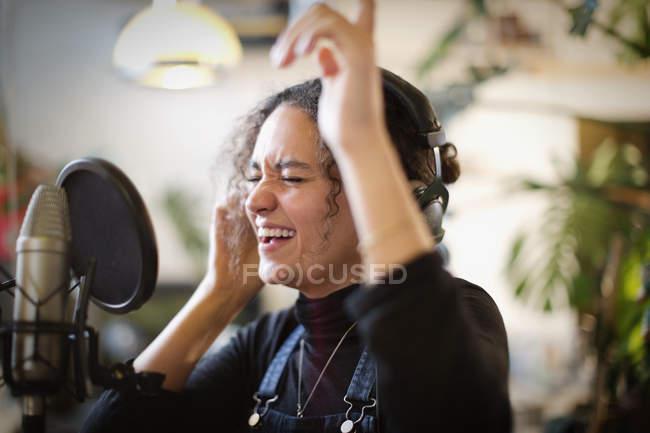 Молодая женщина, запись музыки, петь в микрофон — стоковое фото