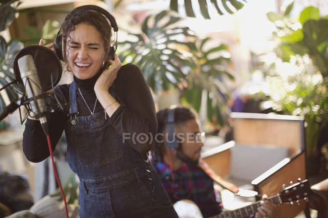 Mulher jovem, gravação de música, cantando para microfone — Fotografia de Stock