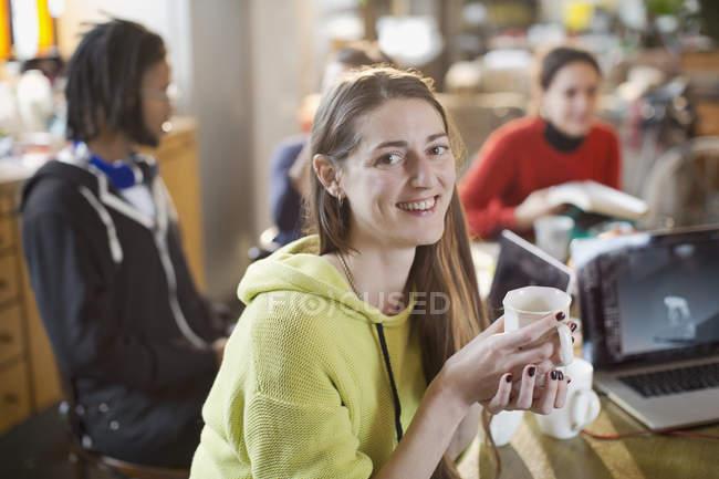Портрет уверенно молодая женщина, пить кофе на кухонный стол с соседями — стоковое фото