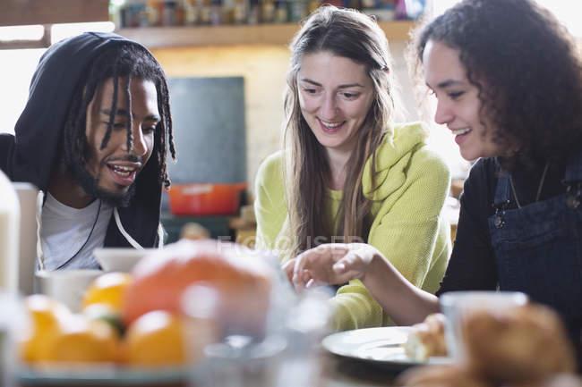 Amici di giovane compagno di stanza utilizzando la tavoletta digitale al tavolo colazione — Foto stock