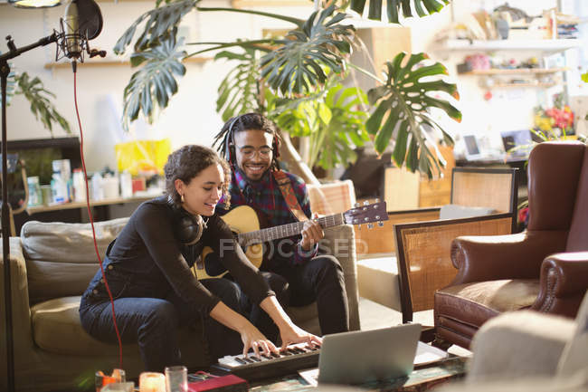 Hombre joven y mujer grabando música, tocar guitarra y teclado piano en Apartamento - foto de stock