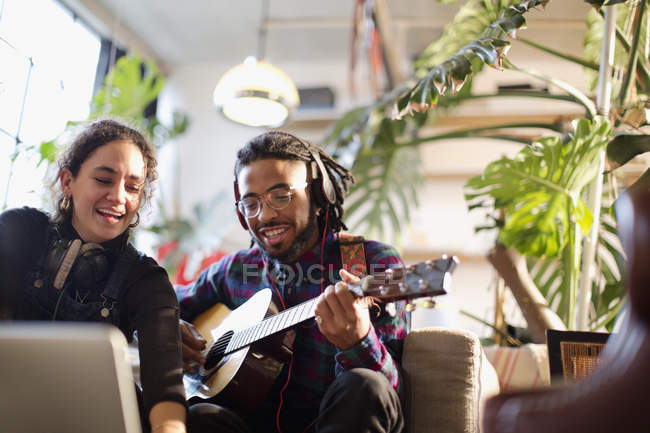 Young man and woman recording music, playing guitar in apartment — Stock Photo