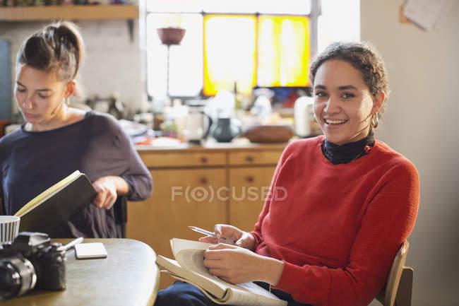 Retrato sorridente feminino estudante estudar na mesa da cozinha no apartamento — Fotografia de Stock