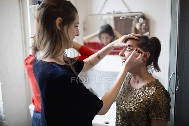 Молодые женщины, готовясь, нанесения макияжа в ванной комнате — стоковое фото
