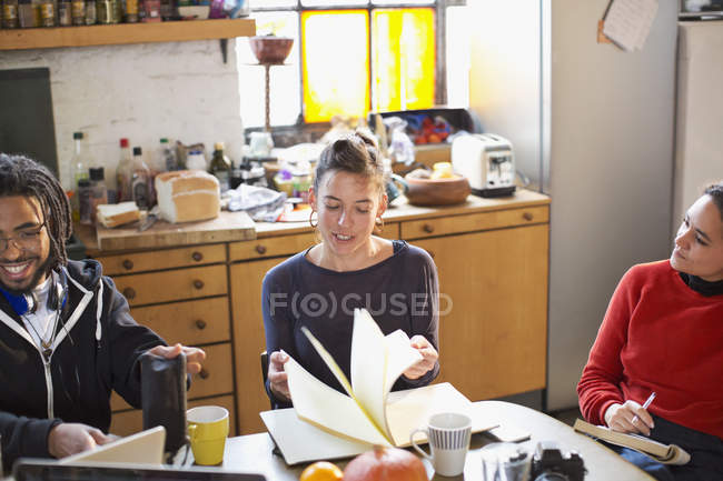 Young college student roommates studying at kitchen table in apartment — Stock Photo