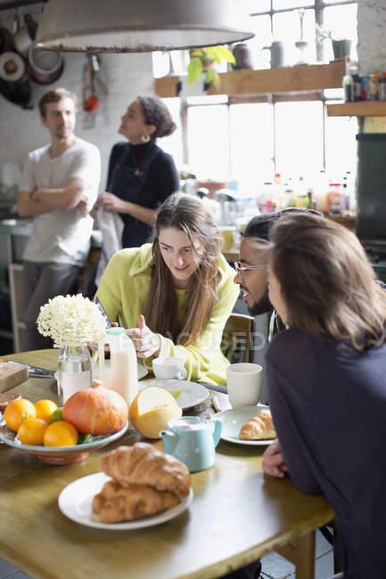Compañeros de estudiante joven de la Universidad hablando en la mesa de la cocina en Apartamento - foto de stock