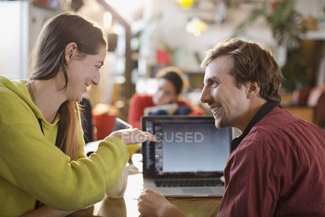 Couple using laptop at table — Stock Photo