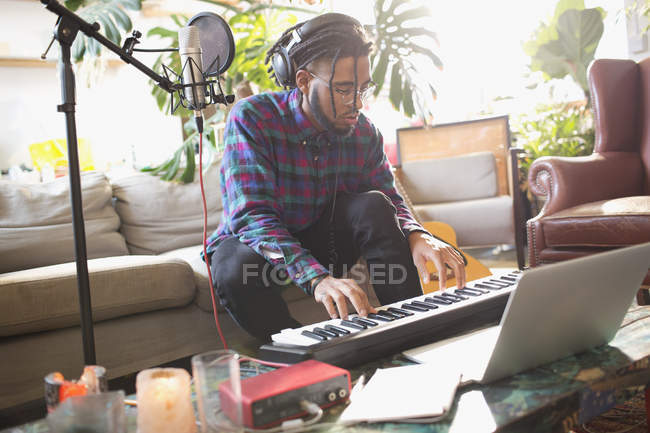 Young man recording music, playing keyboard piano in apartment — Stock Photo