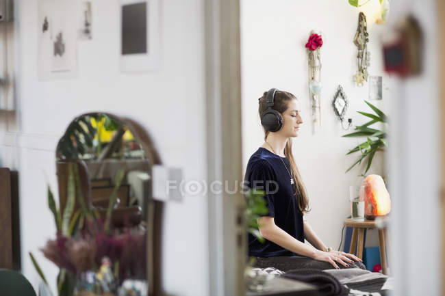 Serene young woman meditating with headphones in apartment — Stock Photo