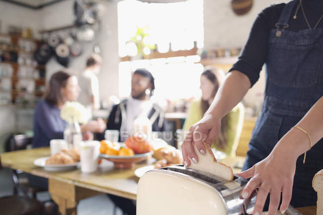 Woman using toaster, eating breakfast in apartment kitchen — Stock Photo