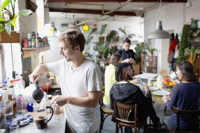 Compañeros de cuarto preparando café y disfrutar de un desayuno en la cocina - foto de stock